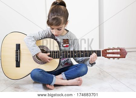 9 Year Old Girl Learning To Play The Guitar.