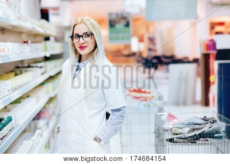 Professional Female Pharmacist Standing In Phamarcy Drugstore And Smiling. Details Of Pharmaceutical