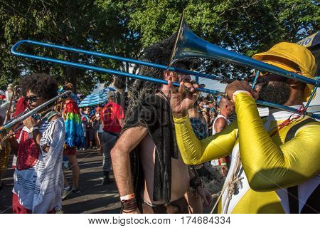 RIO DE JANEIRO, BRAZIL - FEBRUARY 28, 2017: Musicians playing trombones on the background of crowd of costume people at Bloco Orquestra Voadora in Flamengo Park, Carnaval 2017
