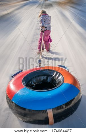 Little girl pulling her colorful inflatable tube after sliding downhill a snowy and icy hill track