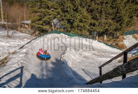 Little girl sledding downhill a snowy and icy hill track on a colorful inflatable tube