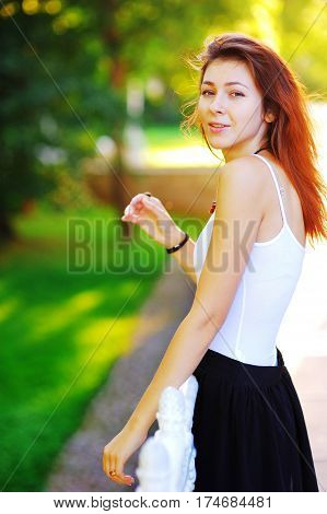 Wonderful portrait of a young smiling woman with beautiful brown hair wearing a white shirt and black skirt standing in the rays of the setting sun in the summer Park