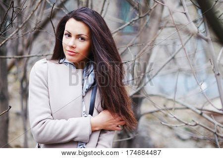 Portrait of a pretty long-haired girl brunettes with beautiful brown eyes in an elegant coat on a blurred background of tree trunks and bare branches closeup.