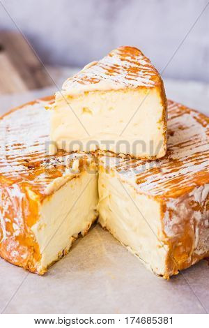 French German soft cheese with orange washed-rind on waxed paper on wood cutting board cut off slice close up rustic