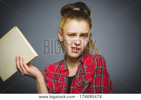wondering and stressed girl with book. Closeup teen on grey background. studies concept.