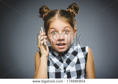 wondering girl with mobile or cell phone. Closeup Portrait of handsome child in casual shirt on grey background.