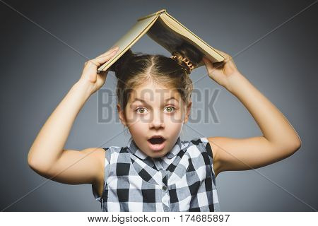 Handsome wondering little girl with book smiling isolated on gray background.