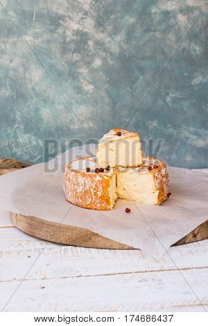French German soft cheese with orange washed-rind fork red pepper corns cutting board rustic style