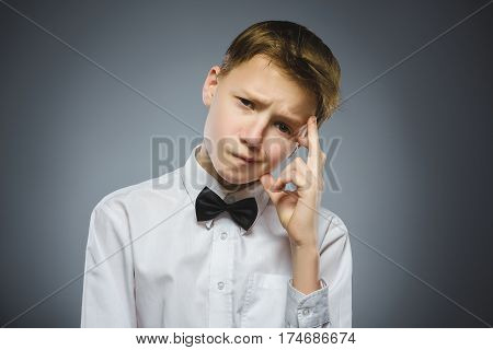 doubt, expression and people concept - boy thinking over gray background.