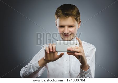 Closeup Portrait happy boy with mobile or cell phone making selfie on gray background