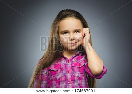 Closeup Thoughtful or contemptuous Young girl Looking Up with hand on glasses isolated on Gray Background.