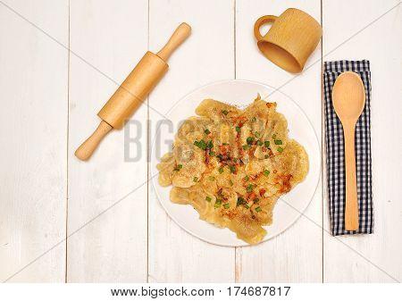 Ukrainian dumplings and cutlery on a wooden background