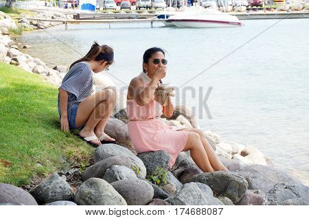 HARBOR SPRINGS, MICHIGAN / UNITED STATES - AUGUST 4, 2016: A woman eats Kilwin's chocolate ice cream, while sitting on a rock along the Harbor Springs waterfront, and enjoying the view of Little Traverse Bay.