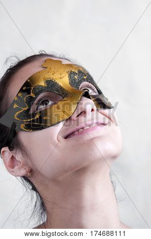 Girl Brunette In A Theatrical Mask Looking Up And Smiling