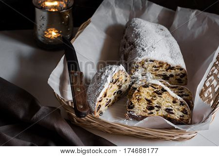 Sliced German Christmas stollen on waxed paper in wicker basket knife linen towel lit candle moody cozy atmosphere minimalistic style