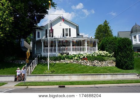 HARBOR SPRINGS, MICHIGAN / UNITED STATES - August 4, 2016:  The Little Traverse Yacht club occupies a Victorian home near the waterfront on Bay Street in Harbor Springs, Michigan.
