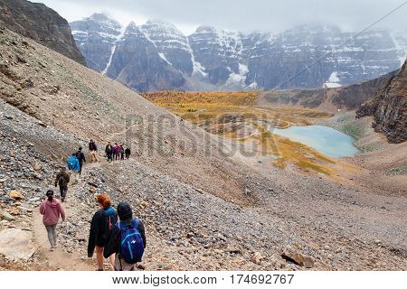 Lake Louise Canada - September 17 2016: Hikers traverse the rocky trail at Sentinel Pass in the Larch Valley near Lake Louise in Banff National Park Alberta with snow-capped Valley of Ten Peaks in the background.