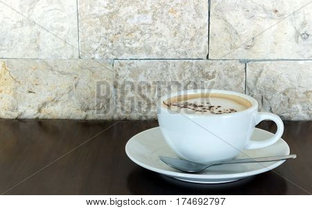 Cup of hot cappuccino on wood table in the coffee shop