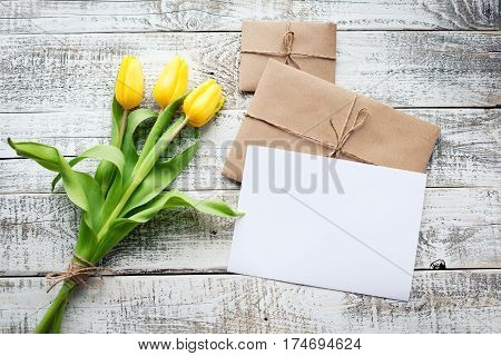 Yellow Tulip Bouquet And Blank Greeting Card. Top View Over Wooden Table