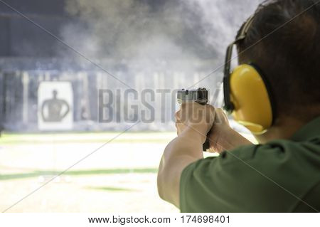 law enforcement aiming and firing gun in academy shooting range surround with smoke and copy space
