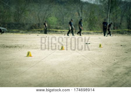 evidence marker with blurred forensic and law enforcement team searching in crime scene training with copy space and cinematic tone