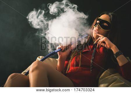 Young, beautiful girl with carnival mask smoke a hookah at club. Sexy woman smoking. Secret. Fashion. Venetian carnival.