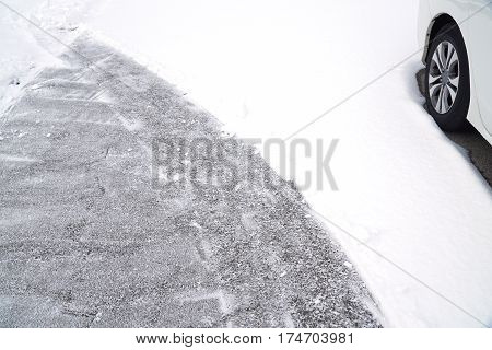 snow removal on the driveway with car in snow