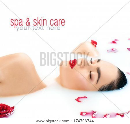 Beautiful Fashion model girl in milk bath, perfect face skin, spa and skin care concept. Beauty young Woman with red rose flower relaxing in milk bath. Healthy spa procedures, rejuvenation