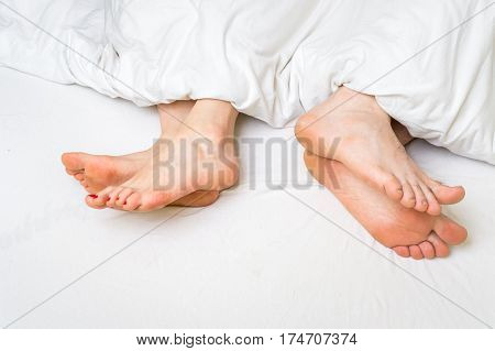 Two Pair Of Feet Far From Each Other In A Bed