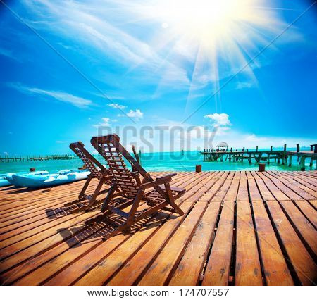 Exotic Beach, Paradise. Travel, Tourism and Vacations Concept. Landscape of Tropical Resort. couple of sun beds waiting for tourists. Jetty near Cancun, Mexico