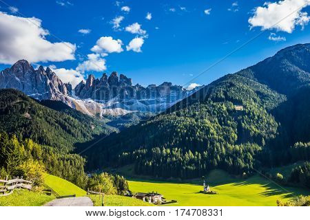 Picturesque little church of Santa Maddalena in valley Val di Funes. Rocky peaks and forested mountains surrounded by green Alpine meadows. Sunny day in Dolomites, Tirol