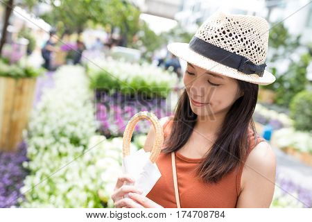 Young Woman holding Spanish churro in flower garden