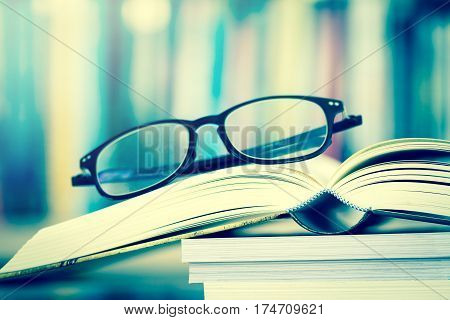 Close up opened book page and reading eyeglasses with blurry bookshelf background for education and publication concept extremely DOF with vintage retro color tone