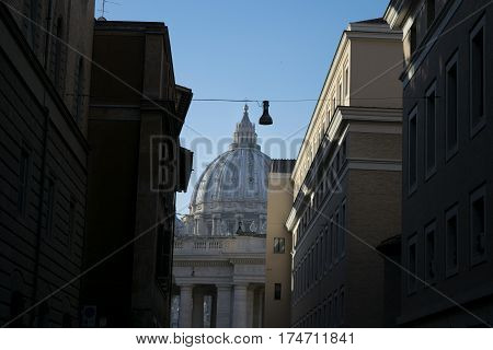Saint Peter's dome in Rome seen through a typical roman alley