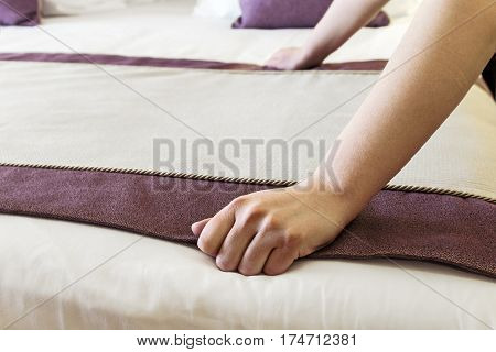 female hands corrected blanket on the bed. Concept on preparation of bed in a hotel room or at home