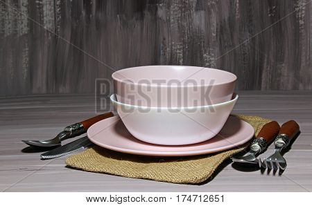 Table setting with porcelain bowls and plate with silverware on wooden background