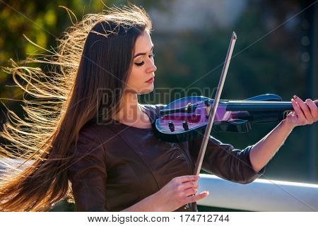 Busker woman perform music on violin in park outdoor. Girl performing jazz on city street . Spring outside with background.