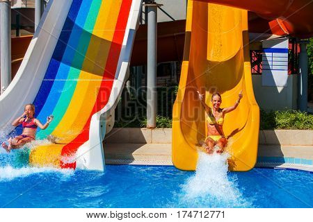 Swimming pool slides for children on water slide at aquapark and thumb up. Summer holiday. There are two kids in aqua park. Outdoor.