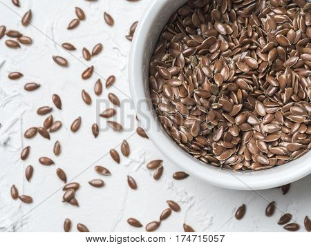 Flax seeds with copy space. Brown flax seed on white concrete textured background. Top view or flat lay. Copy space. Healthy food and diet concept