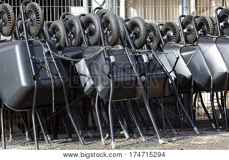 diferent types of black wheelbarrows ready to sell tied with string