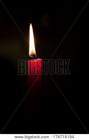Closeup of burning candle on black background