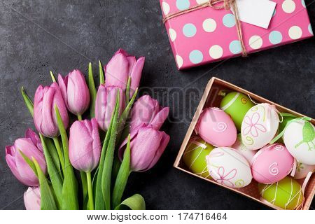 Fresh pink tulip flowers and easter eggs in gift box on stone table. Top view