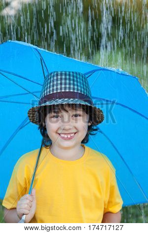 happy boy with umbrella outdoors, child with an umbrella walks in the rain