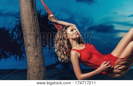 Blonde beauty resting in a hammock on the beach