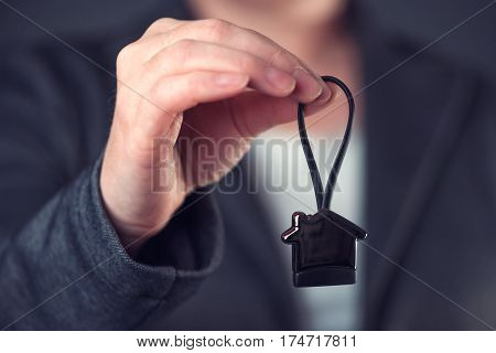 Real estate broker or agent offering house shaped key ring selling or buying a home or apartment