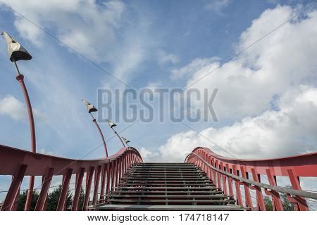 Stairway with red banister in the blue sky with clouds