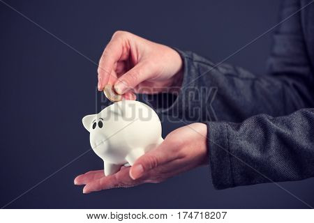 Businesswoman putting one euro coin in piggy bank money savings and home budget concept