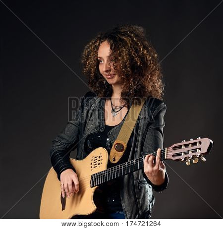 Stylish curly young woman possing with acoustic guitar