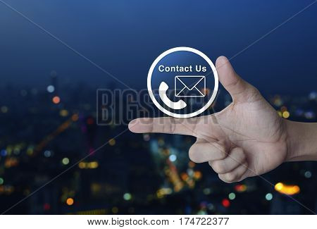 Telephone and mail icon button on finger over blur colorful night light city tower Contact us concept