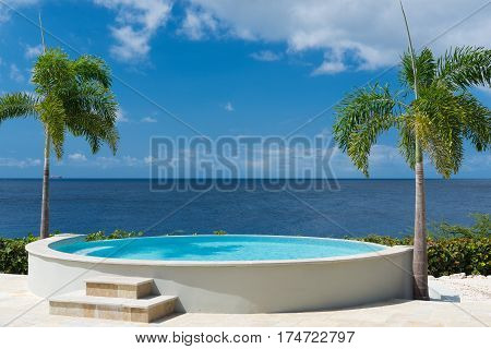 Romantic sunset with round swimming pool and tropical ocean palm trees - Curacao island, paradise on the Earth